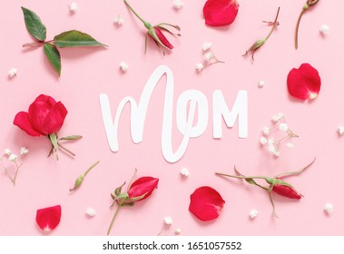 Red roses flowers and word MOM on a light pink background top view