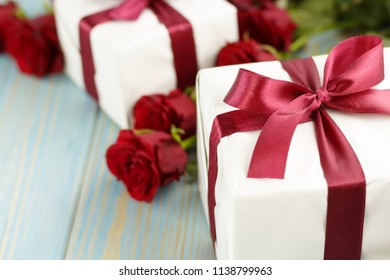 Red roses and gift box on light blue wooden table.