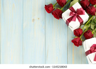 Red roses and gift box on light blue wooden table, top viewed