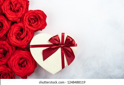 Red roses and gift box in shape of heart on the vintage white-grey background. Festive concept for Valentines day. Top view with copy space.