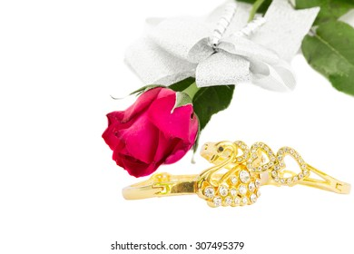 Red roses and Gold bracelet swan and heart shape isolated on white background.