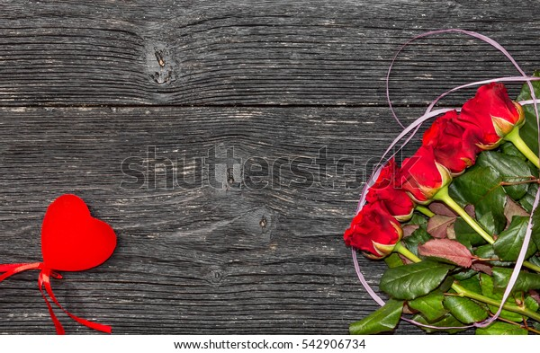 Red roses with red heart on black wooden background. Valentine's card.