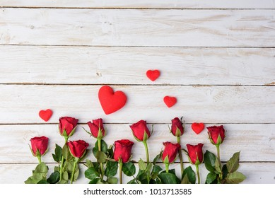 Red roses and hearts on old white wood table/Valentines day background. with copy space