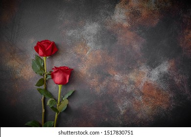 Red roses lie on a textured spotted marble background. A sign of condolence, sympathy for the loss. Space for your text.