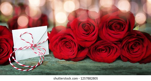 Red roses with a love letter decorated on old rustic wood and bright bokeh for valentines day