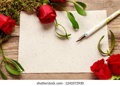 Red roses, mistletoe, moss and blank sheet of paper