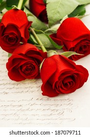 red roses and old love letters. sentimental retro style background with flowers. selective focus