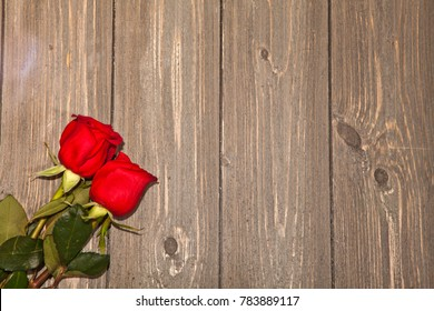 Red roses on barn wood planks with copy space.