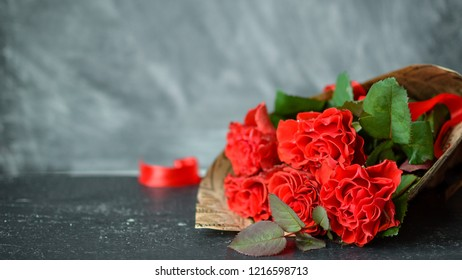 Red roses on the Black wooden table Grey background. Soft selective focus. Copyspase. Happy bithday and Valentine's Day card.