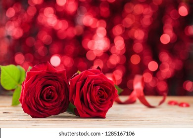 Red roses on old wooden table against holiday lights background.