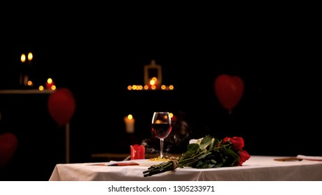Red roses on table near glass of wine, romantic atmosphere, st Valentines Day