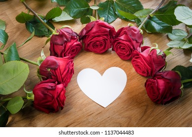 Red roses on a table with a white heart