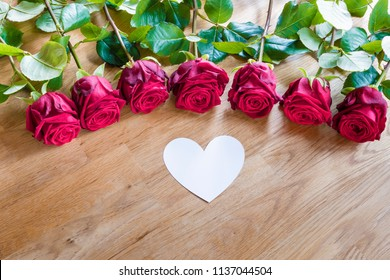 Red roses on a table with white heart
