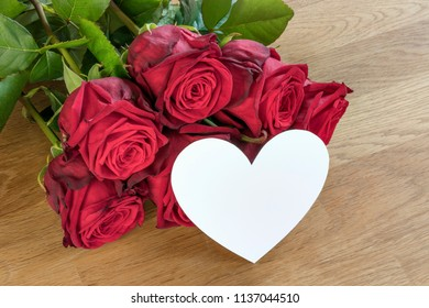 Red roses on a wooden table with white heart