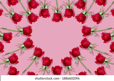 red roses pattern frame in a shape of a heart on a pink background for Valentines Day