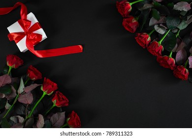 Red roses, ring and gift box on black background