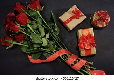 Red roses and three presents with red ribbon on black