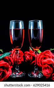 Red roses and two glasses of red wine. Black background