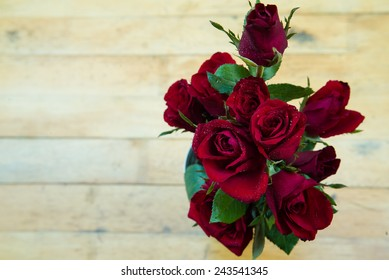 Red roses in vase on the wood table