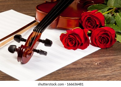 Red Roses And A Violin On The Table