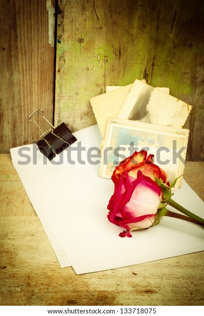 Red roses, white paper and old photos on a vintage wooden background