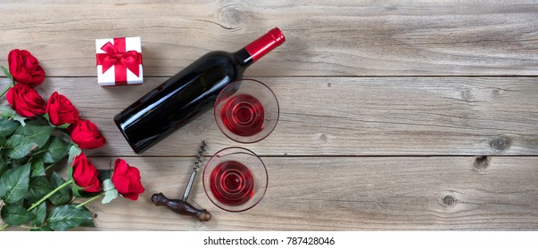 red roses and wine in lower left corner on rustic wood in flat lay view