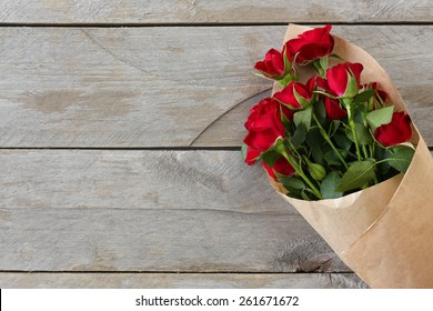 Red roses wrapped in paper on wooden table background