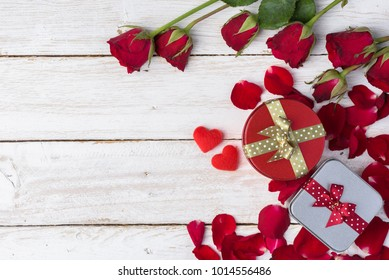 Red roses/petals and gift box on old white wood table/Valentines day background