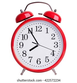 Red round alarm clock shows five minutes to eight