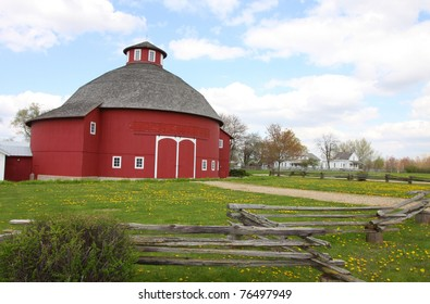 A red round barn with an old wooden fence