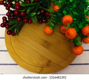 red round berries, fresh ripe juicy orange tangerines with green leaves, on a round wooden Board, hot red chili pepper