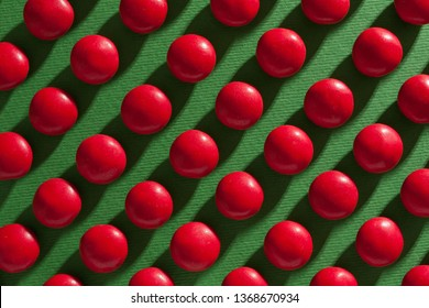 Red round chocolate candies on a green background with a tight shadow