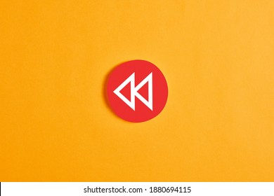 Red round circle with a rewind button against yellow background.
