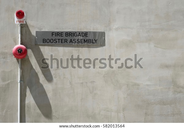 Red round fire alarm bell and Fire brigade sign on grey concrete wall.