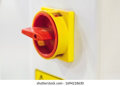 Red round plastic machine switch, close-up photo with selective soft focus