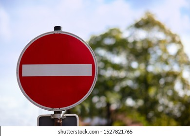 A red round sign warns: entrance forbidden. It is a one way street. In the background a tree, out of focus with beautiful bokeh.