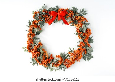 red rowan wreath frame with bow on white background. flat lay, frame wreath, autumn wallpaper