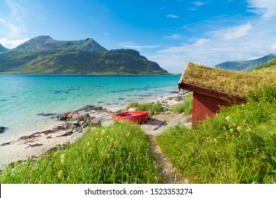 red rowing boat at a beautiful blue fjord on the Lofoten islands in Norway