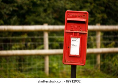A red Royal Mail post box on a post in a country location