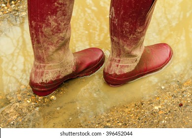 Red rubber boots in muddy puddle