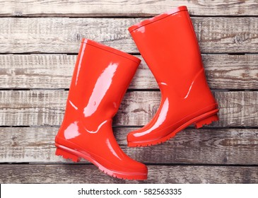 Red rubber boots on a brown wooden table