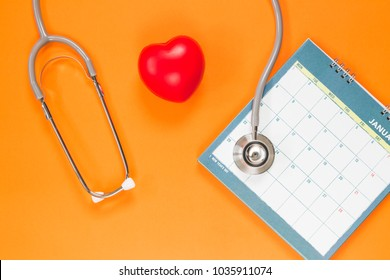 red rubber heart and stethoscope with calendar on orange background, health concept