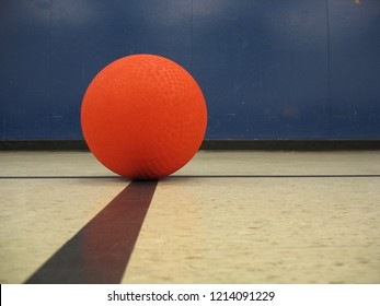 red rubber playground ball on black lines in gymnasium