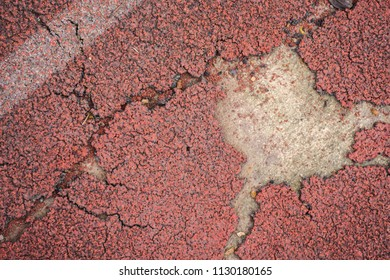 Red rubber sheet of treadmill or running track surface at outdoor playground and stadium torn and rend texture background