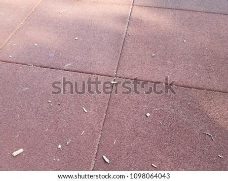 red rubberized surface with wood chips