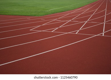 red running road track with white marking lines near green football field and empty space for copy or text
