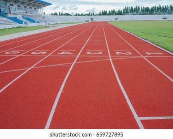 Red running track with blue sky background