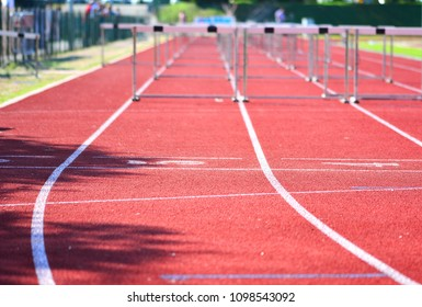 Red running track with hurdles set up for the race.