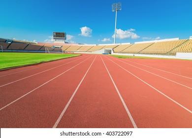 Red running track in stadium on blue sky.