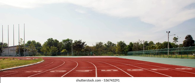 Red running track with white numbers, lines and starting line on outdoor stadium with grass around tracks